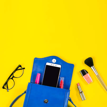 Woman purse, beauty products, smartphone, glasses on a bright yellow background, top view Stok Fotoğraf