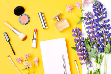 Modern woman accessories. Beauty products, note book, accessories, flowers on a pastel background Stock Photo