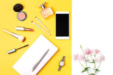 yellow notepad: Modern woman accessories. Beauty products, smartphone, note book, accessories on a pastel background