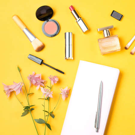Beauty products and pink note book flat lay on pastel background, top view Stock Photo