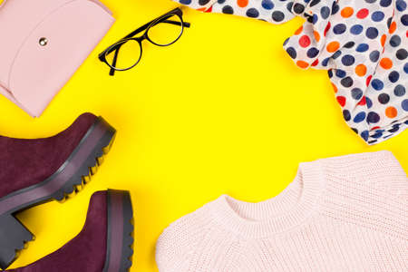 Trendy female autumn clothing. Stylish purple suede ankle boots, pink sweater, purse, glasses and printed scarf