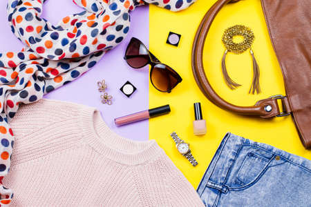Autumn female clothing - pink sweater, blue jeans, leather handbag, printed scarf, accessories and make up products