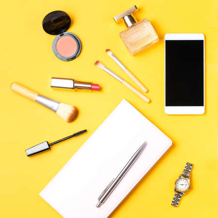 Modern woman accessories. Beauty products, smartphone, note book, accessories on a pastel background