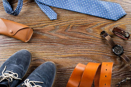 Mens shoes and accessories flat lay on a wooden background. Stock Photo