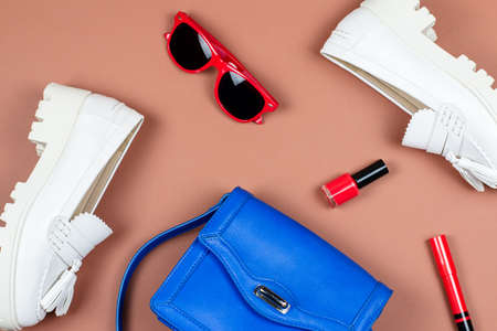 Female white loafers, blue purse and red accessories flat lay