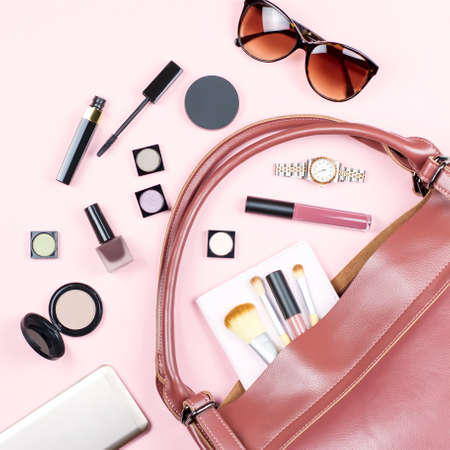 Fashion woman feminine flat lay with beauty products and accessories on pink background