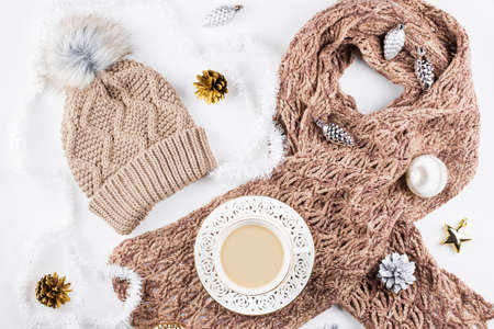 Winter concept flat lay. Warm, cozy winter clothing, hot drink, Christmas decorations frame on white background.