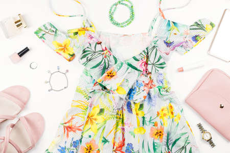 Woman summer dress, accessories and make up items on white background. Summer fashion collection