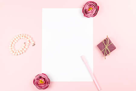 Blank paper card with pen, jewelry, flowers frame on pastel background. Top view, copy space. Imagens