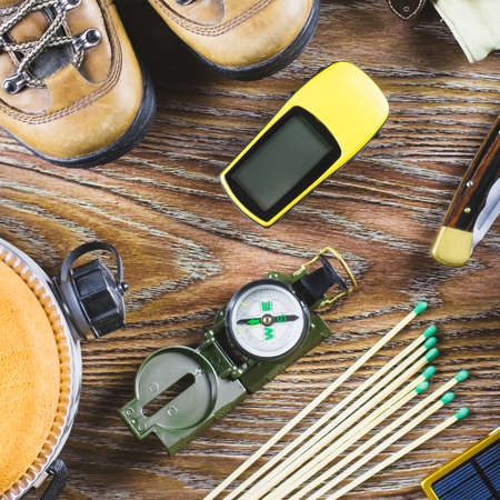 Hiking or travel equipment with boots, compass, binoculars, matches on wooden background. Active lifestyle concept.