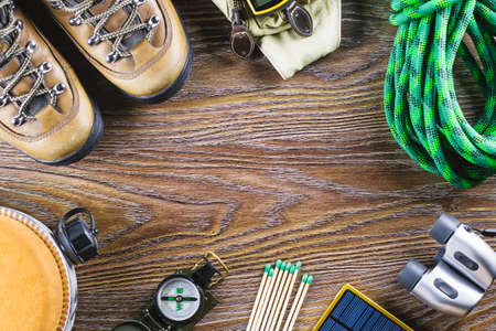 Hiking or travel equipment with boots, compass, binoculars, matches on wooden background. Active lifestyle concept. Top view