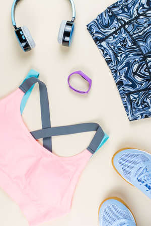 Woman sport clothes, sneakers, headphones and fitness tracker on neutral background. Sport fashion concept. Flat lay Stockfoto