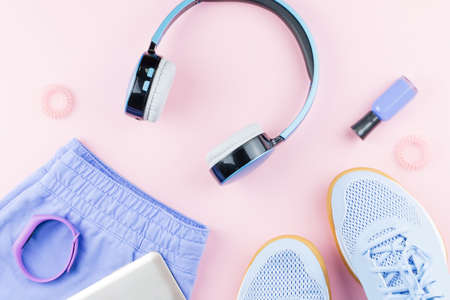 Woman sneakers, headphones, fitness tracker and smartphone on pastel pink background. Sport fashion concept. Flat lay, top view