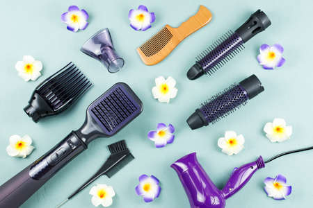 Hairdressing tools with flowers on blue wooden background Фото со стока
