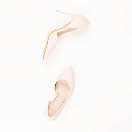 Woman pale pink pumps on pink and white background. Top view, copy space, minimal background. Fashion concept
