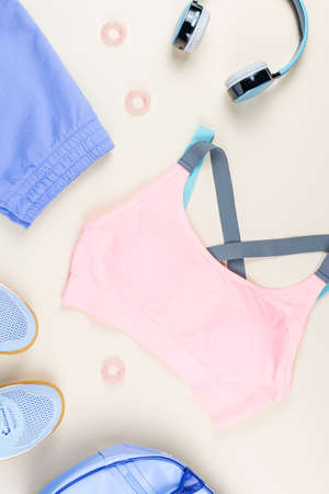Woman sport clothes, sneakers, headphones and fitness tracker on neutral background. Stockfoto