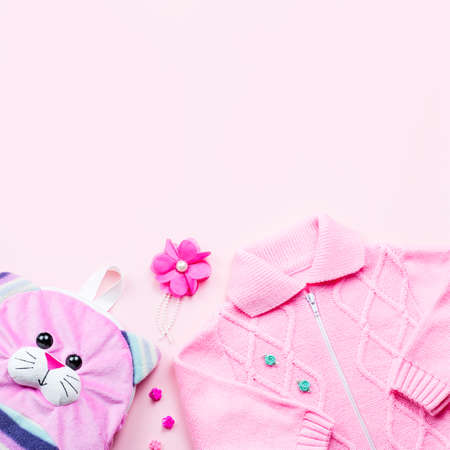 Little girl clothes collection flat lay with cardigan, backpack on pink background. Top view