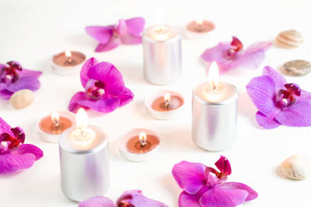 Burning candles and orchid flowers on wooden background. Relaxation spa concept. Top view