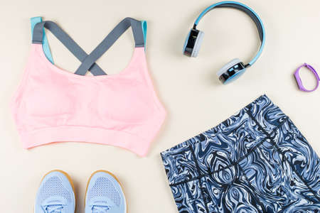 Woman sport bra, leggins, sneakers and fitness tracker on neutral background. Sport fashion concept. Flat lay, top view Stockfoto