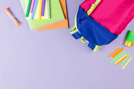 School concept flat lay. Kid backpack, lunchbox, water bottle, notebook, markers on wooden desktop, top view