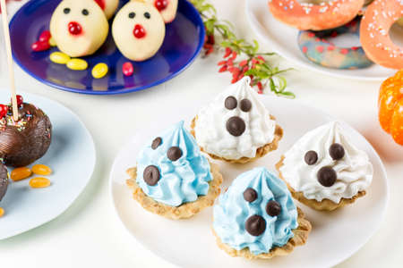 Halloween sweet treats, party food concept. White and blue cakes with faces close up. Top view Stock Photo