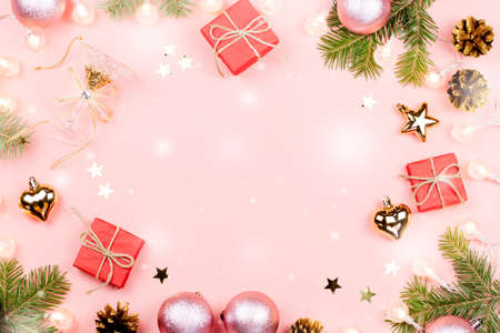 Christmas background with fir tree branches, red giftboxes, decorations, hot drink with marshmallows on pink. Copy space Stock Photo