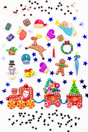 Christmas background with decorations. Santa, Christmas train with tree and sweets, snowman, reindeer and gifts on white background. Copy space Stock Photo