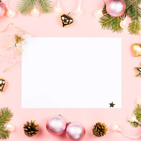 Christmas background with fir tree branches, red giftboxes, decorations, hot drink with marshmallows on pink.