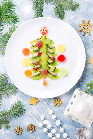 Christmas tree made of kiwi and fruit jelly on a plate with fir branches and decorations Stock Photo