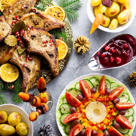 Delicious Christmas meal with roasted meat steak, Christmas Wreath salad, baked potato, grilled vegetables, cranberry sauce. Stock Photo