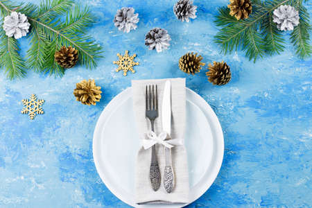 Christmas table setting with plates, silverware, gift box and decorations on blue table. Top view