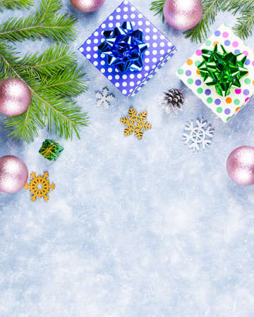 Festive Christmas background with fir branches, Christmas symbols, giftboxes, colorful decorations, copy space. Top view Foto de archivo