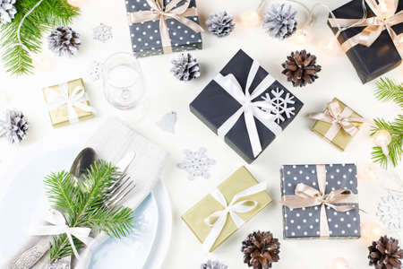 Christmas table setting with plates, silverware, presents and decorations . Top view Stock Photo