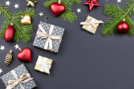 Festive Christmas background with fir branches, presents, decorations on black, copy space Stock Photo