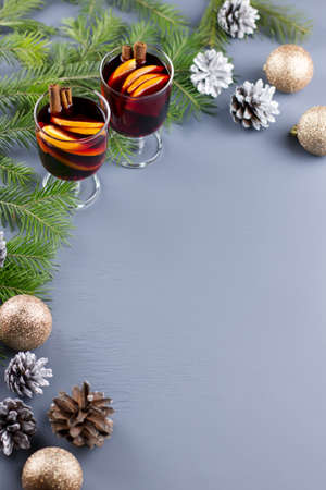 Two glasses of hot mulled wine with spices and sliced orange. Christmas drink with decorations. Top view