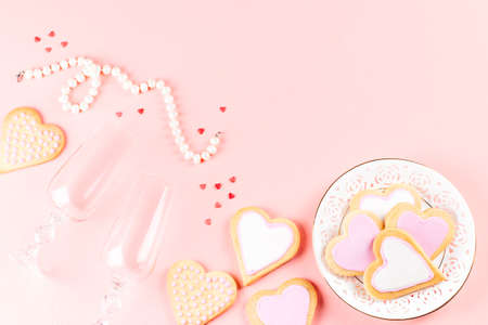Valentine's day cookies, wine glasses and wine on pink background. Top view Imagens