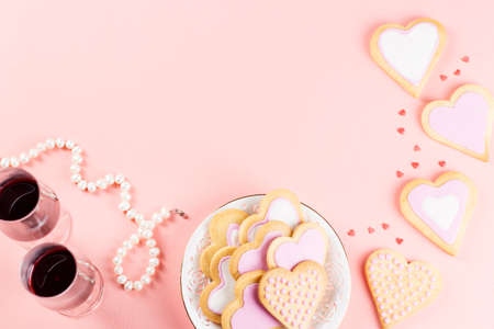 Valentines day cookies, wine glasses and wine on pink background. Top view