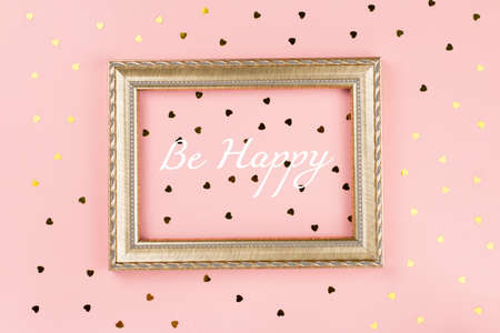 Golden photo frame with text, golden confetti on pastel pink background. Valentines day background. Top view