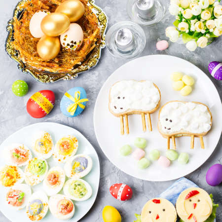 Funny colorful Easter food for kids with decorations on table. Easter dinner concept, top view Stock Photo