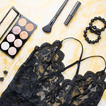 Black lace lingerie with beauty care products, make up cosmetics, jewelry. Fashion flat lay