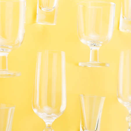Collection of various glasses on bright yellow background