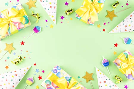 Birthday party background with wrapped gifts, confetti, party hats, decorations