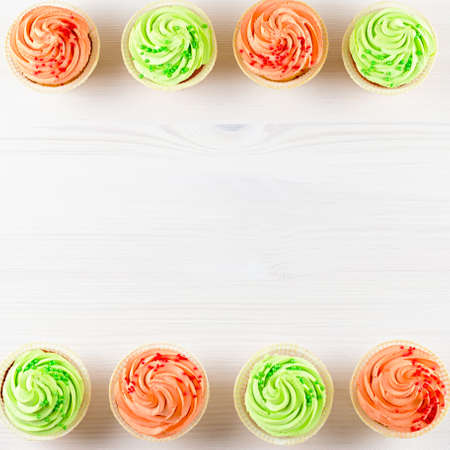 Tasty colorful cupcakes closeup on white wooden background Stock Photo