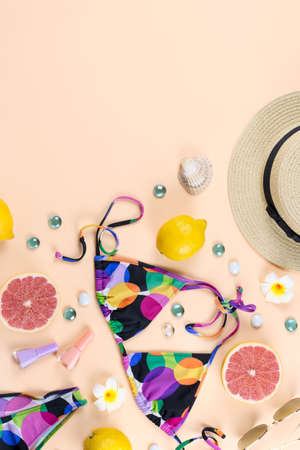 Woman bikini swimsuit with straw hat, flowers and fruits, flat design, tropical summer concept. Beach destination, summer fashion flat lay