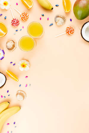 Colorful summer concept flat lay with fresh juice, tropical fruits, lollipops and multicolor seashells