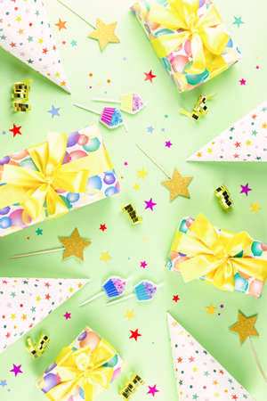 Birthday party background with wrapped gifts, confetti, party hats, decorations, top view