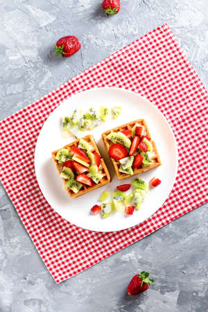Belgian waffles with fruits strawberries and kiwi on white plate Banque d'images - 124866594