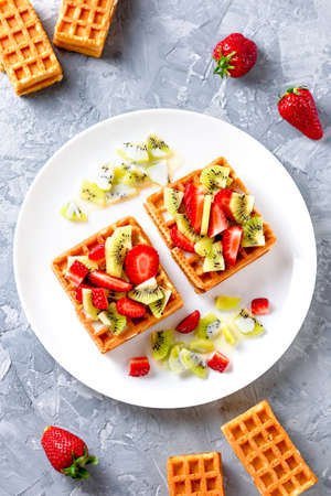 Belgian waffles with fruits strawberries and kiwi on white plate Banque d'images - 124866606
