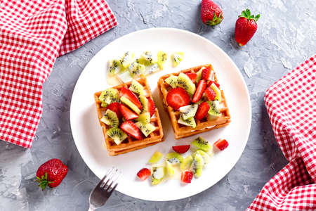 Belgian waffles with fruits strawberries and kiwi on white plate Banque d'images - 124866613