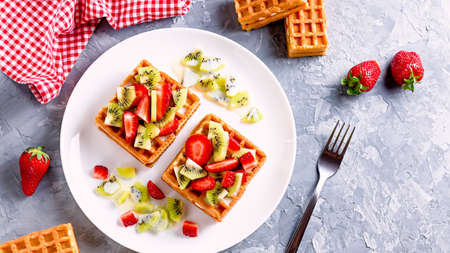 Belgian waffles with fruits strawberries and kiwi on white plate Banque d'images - 124866700